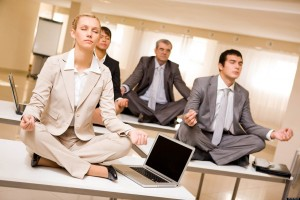 Portrait of meditating partners sitting on desks with their legs crossed in office; Shutterstock ID 39158518; PO: The Huffington Post; Job: The Huffington Post; Client: The Huffington Post; Other: The Huffington Post