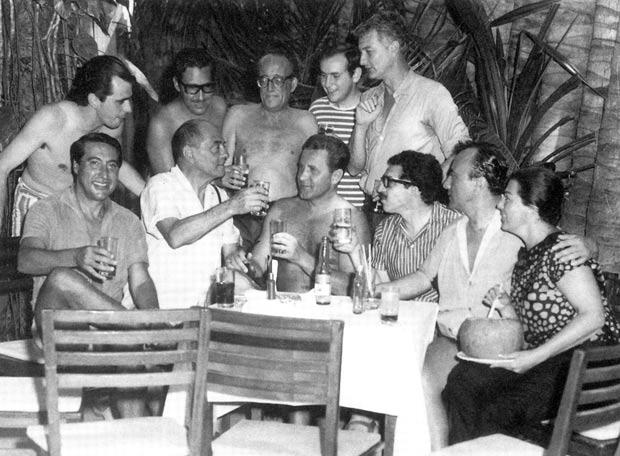 Gabo de gafas oscuras, sentado, Luis Buñuel a su derecha brindando
